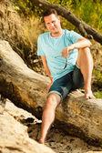 Hombre guapo sentado en árbol por el mar — Foto de Stock