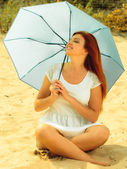 Redhaired girl with umbrella on beach — Stock Photo