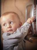 Kid playing with timer of microwave oven — Stock Photo