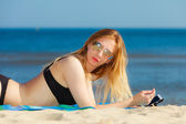 Girl with phone tanning on beach — Stock Photo