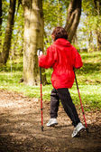 Nordic walking. Woman hiking in the forest park. — Stock Photo