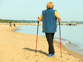 Active woman senior nordic walking on a beach. from behind — Stock Photo