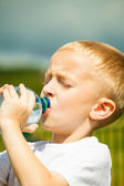 Little boy drink water from bottle, outdoor — Stock Photo