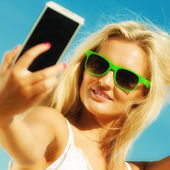Happy girl taking self picture with smartphone — Stock Photo