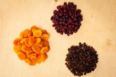 Dried fruits raisins apricots cranberries on table — Stock Photo