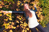 Fall. Girl lying on leaves in autumnal park forest — Stock Photo