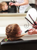 In hair salon. Little girl child sitting by hairdresser combing hair — Stock Photo