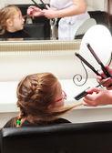 In hair salon. Little girl child sitting by hairdresser combing hair — ストック写真