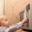 Boy child kid playing with timer of microwave oven — Stock Photo #51547131