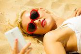 Teen girl with mobile phone on beach — Stock Photo