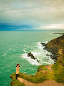 Irish atlantic coast. Woman tourist standing on rock cliff — Foto de Stock