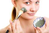Skin care. Woman applying clay mud mask on face. — Stock Photo