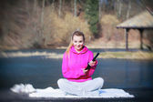 Sport teenage girl using tablet touchpad on pier — Stock Photo