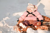 Baby girl sitting on snow — Stock Photo
