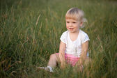 Baby girl sitting in grass — Stockfoto