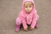 Little girl sitting on the ground — Stock Photo