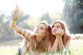 Two girlfriends outdoor looking upwards — Stok fotoğraf