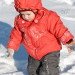 Little girl walking on snow — Stock Photo #28719377