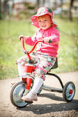 Petite fille sur tricycle — Photo