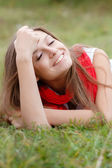 Young female lying down on grass — Stock Photo