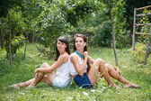 Two young females sitting on grass — Stock Photo