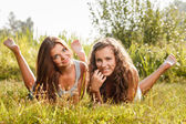 Two girlfriends lying down on grass — Stock Photo