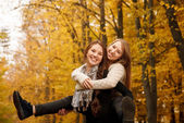 Piggyback ride in autumn forest — Stock Photo