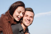 Young male giving his girlfriend piggyback ride — Stock Photo