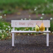 Love couple sitting on the bench with inscription i love you — Stock Photo
