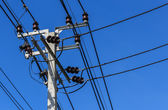 Electric Pole with Powerlines against Bright Blue Sky — Stock Photo