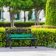 Green Bench in the Park with White Building Background — Stock Photo