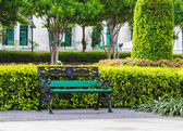 Green Bench in the Park with White Building Background — Zdjęcie stockowe