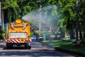 Watering in Public Park with Big Tank Sprayer showing Water mist Droplets — Stock Photo