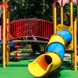 Colorful Spiral Tube Slide on Green Elastic Rubber Floor for Children in the Park — Stock Photo #28943725