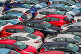 Brand new Motor Vehicles crowed in a Parking lot waiting for Distribution to Dealers — Stock Photo
