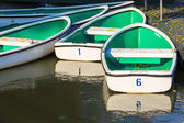 White Rowboats moored at small Pier with Falling Yellow Flowers on the Floor — Stockfoto