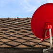 Red Satellite TV Receiver Dish on the Old Tiles Roof — Stock Photo