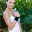 Stock Photo: Beautiful girl smiling holding a bottle of water outdoors