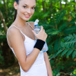 Beautiful girl smiling holding a bottle of water outdoors — Stock Photo