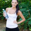 Stock Photo: Beautiful girl laughing holding bottle of water outdoors