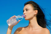 Beautiful brunette girl drinking from a bottle of water — Stock Photo