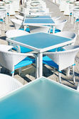 Rows of empty tables and chairs in an open air cafe bar — Stock Photo