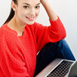 Beautiful smiling girl holding a laptop. — Stock Photo