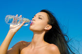 Beautiful brunette girl drinking from a bottle of water. — Stock Photo