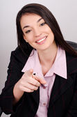 Young smiling business woman pointing finger at viewer — Stock Photo