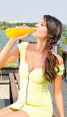 Bella ragazza bruna che bere succo d'arancia da una bottiglia di plastica. — Foto Stock