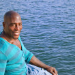 Black man relaxing at the edge of the water. — Stock Photo