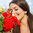 Stock Photo: Beautiful womin garden smelling flowers.