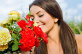 Beautiful woman in the garden smelling flowers. — Stock Photo