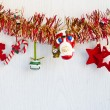 Christmas decorations hanging from red and yellow tinsel. — Stock Photo #31178291